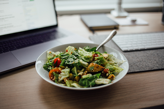 A fresh salad bowl on a desk next to a laptop.